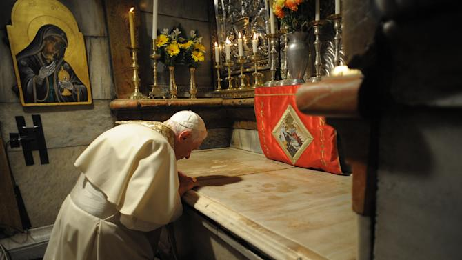 FILE - In this Friday, May 15, 2009 file photo provided the Vatican newspaper L'Osservatore Romano, Pope Benedict XVI prays at the sepulchre, the traditional site where Jesus was buried, inside the the Church of the Holy Sepulcher, in Jerusalem's Old City. (AP Photo/L'Osservatore Romano, File)