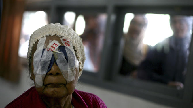 In this Sunday, Nov. 11, 2012 photo, an elderly woman waits for her eye patches to be removed following her cataract surgery at Putri Hijau military hospital in Medan, North Sumatra, Indonesia. Indonesians flocked to the hospital for free cataract surgery performed by a team led by Nepalese master surgeon Dr. Sanduk Ruit who is renowned for his high-volume assembly-line approach. During the eight-day eye camps held in two towns in North Sumatra, more than 1,400 cataracts were removed. (AP Photo/Binsar Bakkara)
