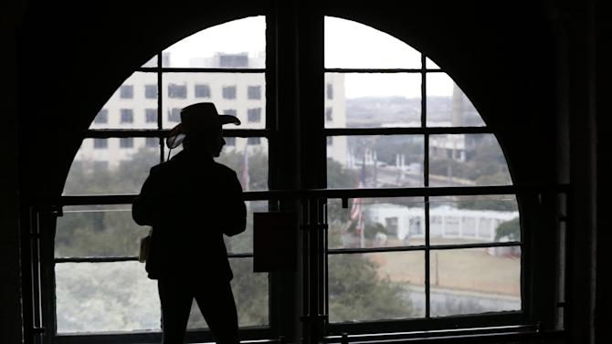 FILE - In this photo made Jan. 25, 2013, a visitor wearing a cowboy hat looks out onto Dealey Plaza from the Sixth Floor Museum located in the former Texas School Book Depository building in Dallas. Three cities loom large in the life and death of John F. Kennedy: Washington, D.C., where he served as U.S. president and as a senator; Dallas, where he died, and Boston, where he was born. With the 50th anniversary of his Nov. 22, 1963 assassination at hand, all three places are worth visiting to learn more about him or to honor his legacy. (AP Photo/LM Otero)