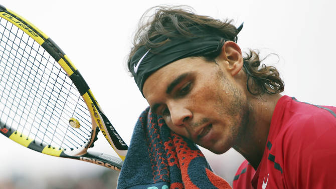 FILE - In this June 10, 2012, file photo, Spain's Rafael Nadal wipes his face as he plays Serbia's Novak Djokovic during their men's final match in the French Open tennis tournament at the Roland Garros stadium in Paris. Nadal will miss the Australian Open because of a stomach virus, further delaying his comeback after being sidelined since June.(AP Photo/David Vincent, File)