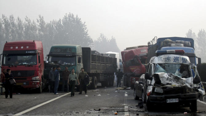 In this photo taken on Friday, Oct. 7, 2011, people look at the damaged vehicles piled up on a highway road in Huaibei in central China's Anhui province. Three major road accidents in China killed at least 56 people on the last day of a weeklong holiday, including 35 people who died after a bus collided with a car on a northern expressway, state media reported Saturday. (AP Photo) CHINA OUT
