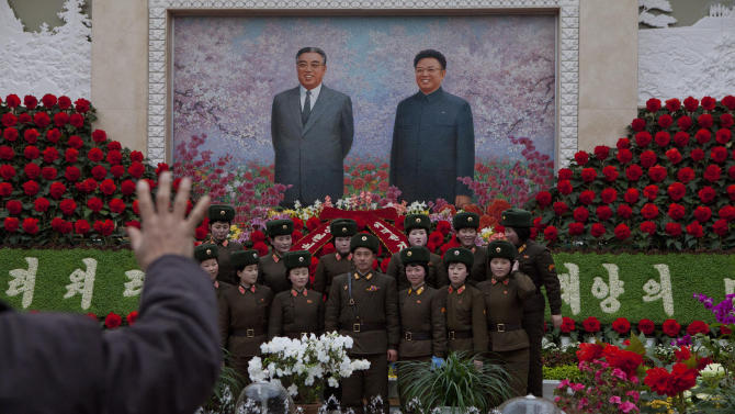 A North Korean portrait photographer instructs North Korean soldiers to pose for a picture under a mosaic of the late leaders Kim Il Sung and Kim Jong Il at an exhibition in Pyongyang on Sunday, Feb. 17, 2013 where Kimjongilia flowers, named after Kim Jong Il, were on display. (AP Photo/David Guttenfelder)