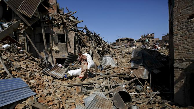 Woman carrying a sack of belongings walks amidst the rubble of collapsed houses after Saturday's earthquake in Bhaktapur, Nepal