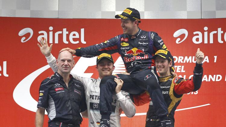 Mercedes driver Rosberg and Lotus F1 driver Grosjean lift Red Bull driver Vettel as he touches the head of Red Bull technical chief Newey after Indian F1 Grand Prix in Greater Noida