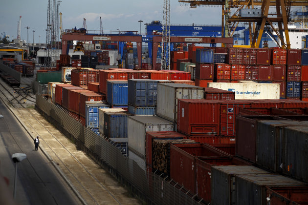 A man walks past containers at Lisbon port during a dock workers strike, Tuesday, Aug. 14, 2012. Portuguese dock workers went on strike against new labor laws that the Portuguese government wants to apply in the sector. The government has been enacting austerity economic measures linked to a euro 78 billion ($96 billion) bailout in 2011. (AP Photo/Francisco Seco)
