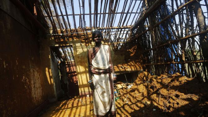 A woman stands inside her damaged house after Cyclone Phailin hit Gopalpur village