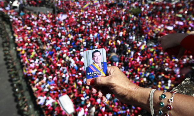 A supporter of Venezuela's late President Hugo Chavez holds a picture of him above a crowd waiting for Chavez's coffin to be taken from the hospital where he died on Tuesday, to a military academy whe
