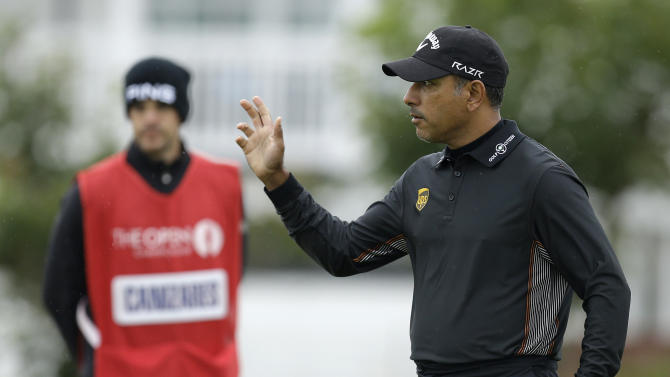Jeev Milkha Singh of India reacts to the crowd after his putt on the 2nd green at Royal Lytham & St. Annes golf club during the first round of the British Open Golf Championship, in Lytham St. Annes, England, Thursday, July 19, 2012. (AP Photo/Jon Super)