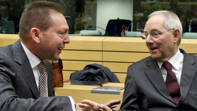 Greek Finance Minister Yannis Stournaras, left, speaks with German Finance Minister Wolfgang Schaeuble during a meeting of eurogroup finance ministers in Brussels on Thursday, Dec. 13, 2012. The European Union on Thursday took a major step towards one of the most important transfers of financial authority away from national capitals when its member states agreed to create a single supervisor for their banks. (AP Photo/Virginia Mayo)