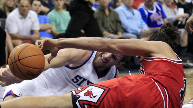 Philadelphia 76ers' Spencer Hawes, left, grabs for the ball on the court with Chicago Bulls' Joakim Noah (13) during the second quarter of Game 3 in an NBA basketball first-round playoff series in Philadelphia, Friday, May 4, 2012. (AP Photo/Mel Evans)