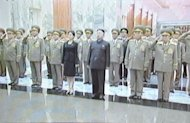 This screen grab taken from North Korean TV on July 9, shows N.Korean leader Kim Jong-Un (C), an unidentified woman and top military officials paying tribute to his late grandfather Kim Il-Sung on the anniversary of his death, at the Kumsusan Palace in Pyongyang. The 'mystery' woman has prompted speculation in Seoul about whether she is his partner or his younger sister