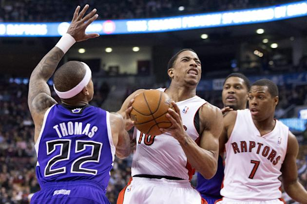 Toronto Raptors' DeMar DeRozan, center, drives to the net past Sacramento Kings' Isaiah Thomas, left, as Kings' Rudy Gay and Raptors Kyle Lowry, right, look on during first half NBA basket