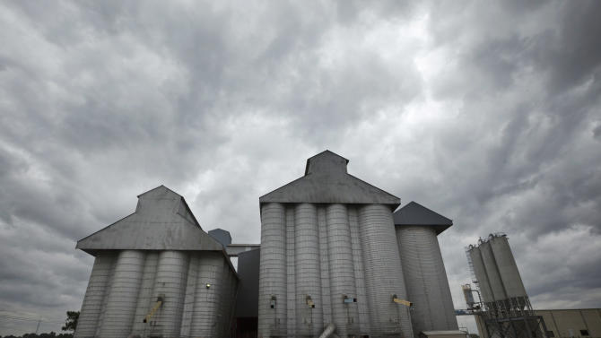 Storm clouds leading remnants of Hurricane Isaac gather in the skies over a grain elevator in England, Ark., as a man carries tools into a gust of wind Thursday, Aug. 30, 2012. With the storms approaching many farm states, some farmers wonder whether too much relief is on the horizon. (AP Photo/Danny Johnston)