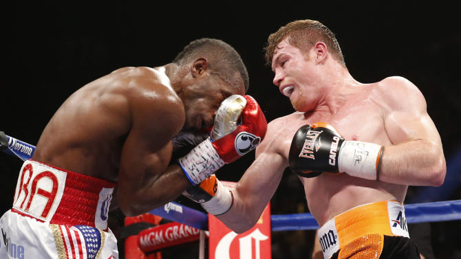 Canelo Alvarez, right, of Mexico, hits Erislandy Lara, of Cuba, during their super welterweight fight, Saturday, July 12, 2014, in Las Vegas