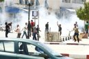 Tear gas is seen as protesters clash with riot police attempting to disperse the crowd in the city of Kairouan