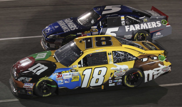 Kyle Busch (18) passes Kasey Kahne (5) in Turn 4 during the NASCAR Sprint Cup Series auto race at Richmond International Raceway in Richmond, Va., Saturday, April 28, 2012. (AP Photo/Zach Gibson)