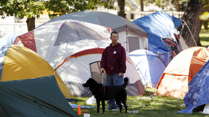 A man walks a dog through the tent city that has been setup at Lincoln Park across from the Capitol in Denver, Colo., on Thursday, Oct. 13, 2011. Colorado Gov. John Hickenlooper said on Thursday that Wall Street protesters near the state Capitol can demonstrate during the day but must tear down their tent camp. (AP Photo/Ed Andrieski)