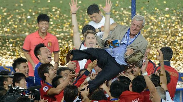 Guangzhou Evergrande coach Marcello Lippi (C) is surrounded by his players after winning their AFC Champions League second leg final football game against FC Seoul in Guangzhou on November 9, 2013. The final score was 1:1. AFP PHOTO / Ed Jones