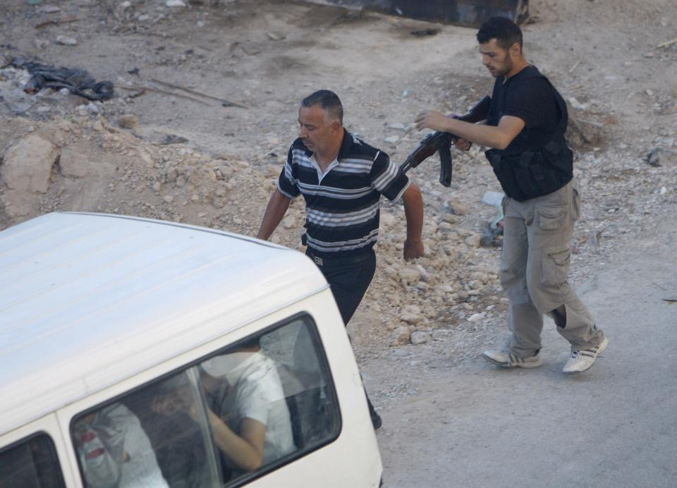 In this Thursday Aug. 2, 2012 photograph, a Syrian rebel fighter detains a man at an improvised checkpoint in a suburb of Damascus, Syria. (AP Photo)