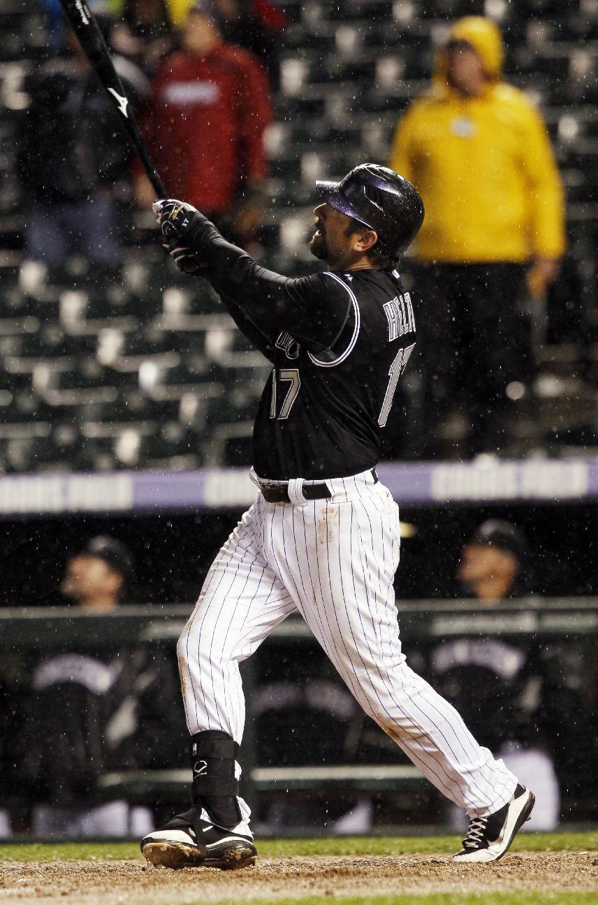 Colorado Rockies' Todd Helton follows the flight of his two-run, walkoff home run against the Arizona Diamondbacks in the ninth inning of the Rockies' 8-7 victory in a baseball game in Denver on Saturday, April 14, 2012. (AP Photo/David Zalubowski)