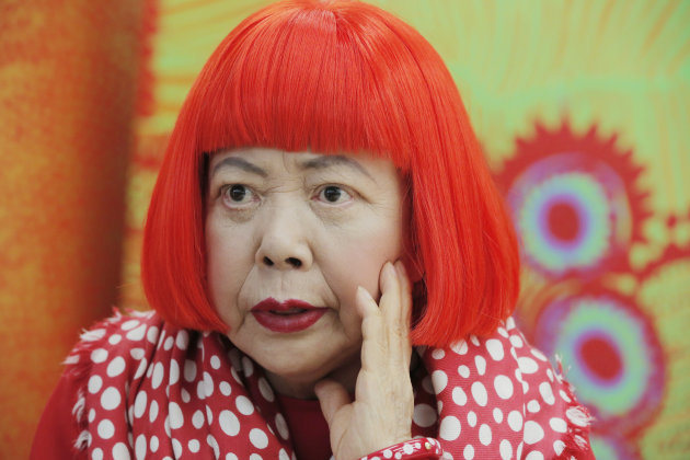 In this photo taken Wednesday, Aug. 1, 2012, Japanese avant-garde artist Yayoi Kusama, wearing a bright red wig and a Louis Vuitton polka dot scarf, speaks during an interview at her studio in Tokyo.