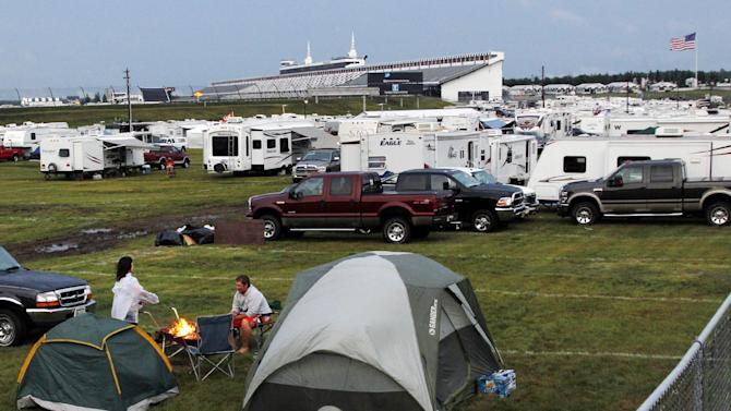 People sit at a campfire in a lot near the grandstands after the NASCAR Sprint Cup Series auto race, Sunday, Aug. 5, 2012, at Pocono Raceway in Long Pond, Pa. A lightning strike in the parking lot at Pocono Raceway after the rain-shortened race killed one person and injured nine others, racetrack officials said. It wasn't immediately clear if all 10 people were actually struck by lightning in the parking lot behind the grandstand, nor was it known whether one or multiple strikes occurred. (AP Photo/Mel Evans)