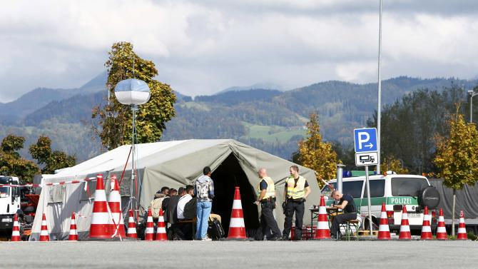 German police officers check passports of bus passengers in a highway services area on A93 highway from Austria to Germany near Kiefersfelden