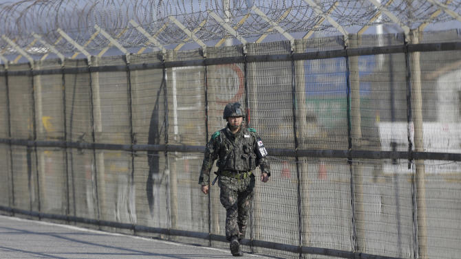 A South Korean army soldier walks along the military wire fences at barricaded Unification Bridge near the border village of Panmunjom, that has separated the two Koreas since the Korean War, in Paju, north of Seoul, South Korea, Wednesday, April 10, 2013. A few hundred South Korean managers, some wandering among quiet assembly lines, were all that remained Tuesday at the massive industrial park run by the rival Koreas after North Korea pulled its more than 50,000 workers from the complex. Other managers stuffed their cars full of finished goods before heading south across the Demilitarized Zone that divides the nations. (AP Photo/Lee Jin-man)