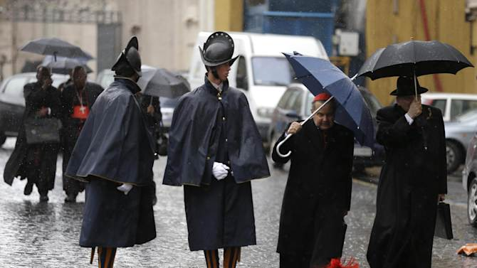"""Cardinal Carlo Caffarra, second from right, and Cardinal Raymond Leo Burke, right, walk past two Swiss guards as they leave after a meeting at the Vatican, Friday, March 8, 2013 The Vatican says the conclave to elect a new pope will likely start in the first few days of next week. The Rev. Federico Lombardi told reporters that cardinals will vote Friday afternoon on the start date of the conclave but said it was """"likely"""" they would choose Monday, Tuesday or Wednesday. The cardinals have been attending pre-conclave meetings to discuss the problems of the church and decide who among them is best suited to fix them as pope. (AP Photo/Alessandra Tarantino)"""