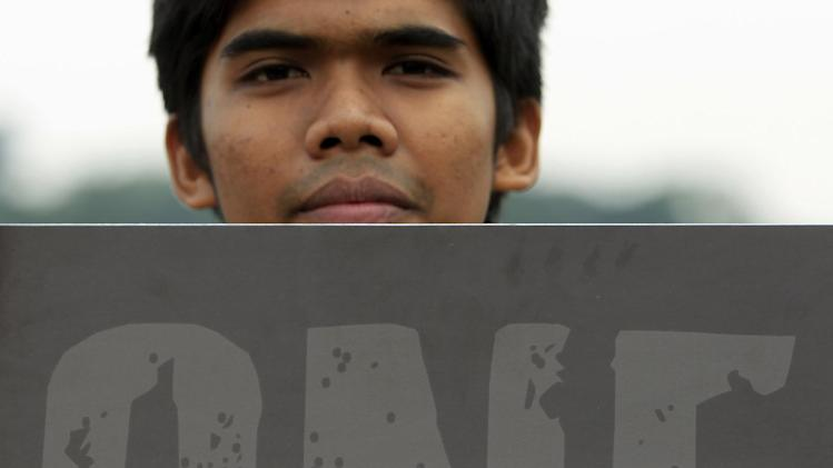 A youth holds a placard during a rally to seek justice for the victims of the Malaysia Airlines Flight 17, outside the Parliament house in Kuala Lumpur, Malaysia, Wednesday, July 23, 2014. A team of Malaysian investigators visited the site along with members of the the Organization for Security and Cooperation in Europe (OSCE) mission in Ukraine for the first time since the air crash last week. (AP Photo/Lai Seng Sin)