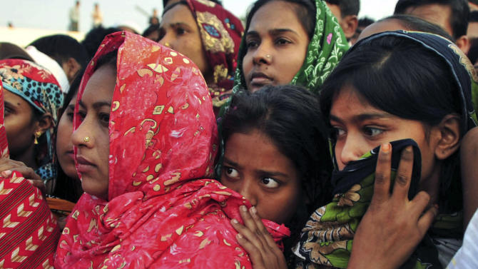 Bangladeshi women watch the bodies of some of the victims of Saturday's fire in a garment factory being prepared to be buried, in Dhaka, Bangladesh, Tuesday, Nov. 27, 2012. Bangladesh held a day of mourning Tuesday for the 112 people killed at the factory, and labor groups planned more protests to demand better worker safety in an industry notorious for operating in firetraps. (AP Photo/Khurshed Rinku)