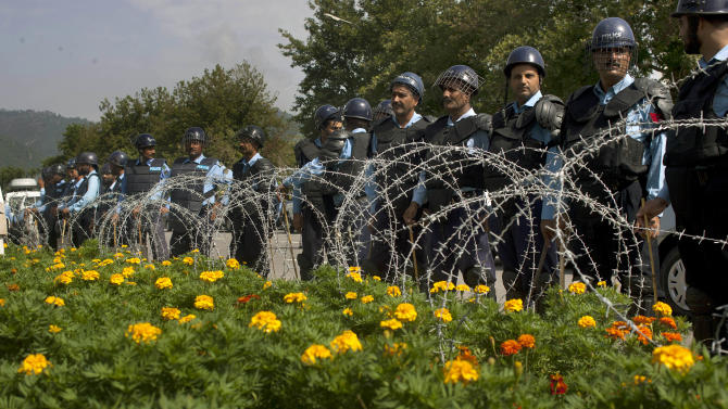 Pakistani police officers stand guard behind barbed-wire outside the Supreme Court, where Prime Minister Raja Pervaiz Ashraf, unseen, is appearing for a hearing in Islamabad, Pakistan on Tuesday, Sept. 18, 2012.  Pakistan's prime minister has agreed to a longstanding Supreme Court demand to reopen a corruption case against the country's president. The decision could defuse tensions over the case that have roiled Pakistan's political system for months and lead to the ouster of the last premier. (AP Photo/Anjum Naveed)