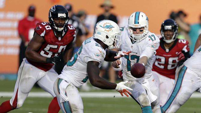 Miami Dolphins quarterback Ryan Tannehill (17) hands the ball to Miami Dolphins running back Lamar Miller (26) during the second half of an NFL football game, Sunday, Sept. 22, 2013, in Miami Gardens, Fla