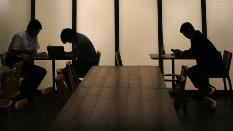 People sit on chairs at a cafe in Tokyo