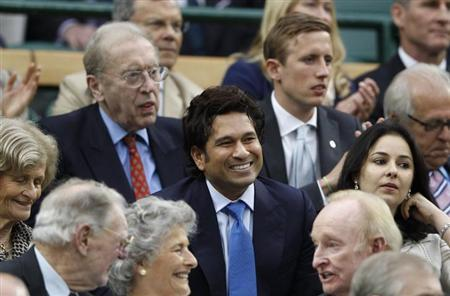 Indian cricket player Sachin Tendulkar (C) sits on Centre Court for the men's semi-final tennis match between Roger Federer of Switzerland and Novak Djokovic of Serbia at the Wimbledon tennis champion