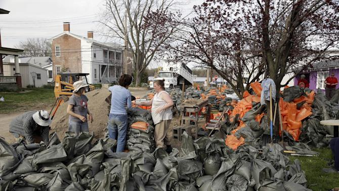 Volunteers work to fill sandbags Monday, April 22, 2013, in Clarksville, Mo. The swollen Mississippi River has strained a hastily erected makeshift floodwall in Clarksville, creating trouble spots that volunteers were scrambling to patch. (AP Photo/Jeff Roberson)