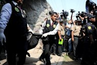 Peruvian policemen carry one of the corpses of the fire victims at the &quot;Sagrado Corazon de Jesus&quot; rehabilitation centre for drug and alcohol addicts in Lima. The disaster comes just three months after 29 people were killed in a fire at another drug rehabilitation center in Lima
