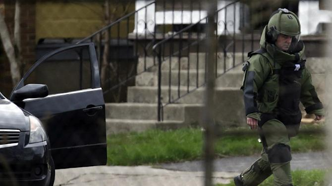 A law enforcement official dressed in bomb protective gear walks near the car where a New York State Police robot removed suspicious packages from the car in Niagara Falls, N.Y., Friday, April 19, 2013.  Trooper Jeffrey Bebak says that a state police bomb disposal team is using a robot to remove items from the car that was stopped earlier in the morning. Bebak says two men are being questioned by police but he has no other details. The response came amid an intense manhunt in Massachusetts one of the Boston Marathon bombers.(AP Photo/David Duprey)