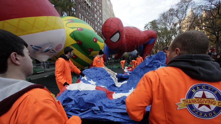 Macy's workers unfold a balloon to be inflated for the 86th annual Macy's Thanksgiving Day Parade, adjacent to the Chloe and Spider-Man balloons, on New York's Upper West Side, Wednesday, Nov. 21, 2012. More than 3 million people typically attend the event and it has a TV audience of 50 million. (AP Photo/Richard Drew)