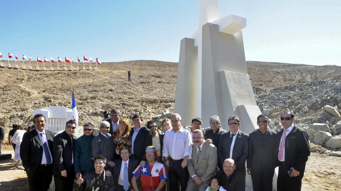 "In this photo released by Chile's Presidency, Chile's President Sebastian Pinera, center, poses for pictures surrounded by the miners who survived in entrapment longer than anyone else before, during an event marking the second anniversary of the cave-in at the San Jose mine in the Atacama in front of a monument on the outskirts of Copiapo, Chile, Sunday, Aug. 5, 2012. Pinera traveled to the northern city of Copiapo to join the men at the mouth of the mine that nearly became their rocky grave. They unveiled a five-meter (16 1/2-foot) cross as part of a monument known as the ""The 33 miners of Atacama: The miracle of life."" (AP Photo/Chile's Presidency)"