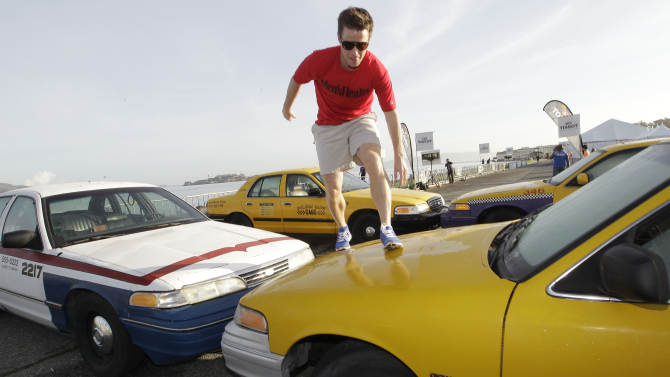 Celebrity hostBilly Bushclimbs over taxicabs during the Men's Health Urbanathlon, Sunday, November 18, 2012 in San Francisco. The Men's Health Urbanathlon is a rigorous 9 mile course, packed with challenging urban obstacles set against the backdrop of iconic city landmarks.(Photo by Tony Avelar/Invision for Men's Health/AP Images)