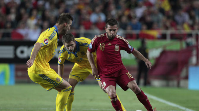 Spain's Jordi Alba fights for the ball against Ukraine's Andriy Yarmolenko, left, and Pylyp Budkivskyi, center,  during the Euro 2016 qualifying soccer match between Spain and Ukraine, at the Ramon Sanchez Pizjuan stadium, in Seville, Spain, on Friday, March. 27, 2015. (AP Photo/Angel Fernandez)