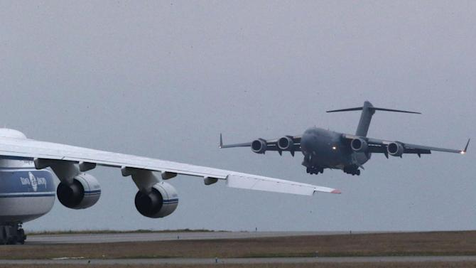 A British C17 transport plane lands next to a Russian Antonov which was hired by the French army to transport equipment to Mali, at the army base in Evreux, 90 kms(56 mls)north of Paris, Monday, Jan. 14, 2013. British military equipment was readied for deployment in Mali on Monday as international intervention in the country increased following advances in the north by Islamic extremists with reported links to Al-Qaida. Two C-17 transport planes have arrived at the French military airbase at Evreux, bound for Mali. Two C-17 transport planes have arrived at the French military airbase at Evreux, bound for Mali. (AP Photo/Michel Euler)