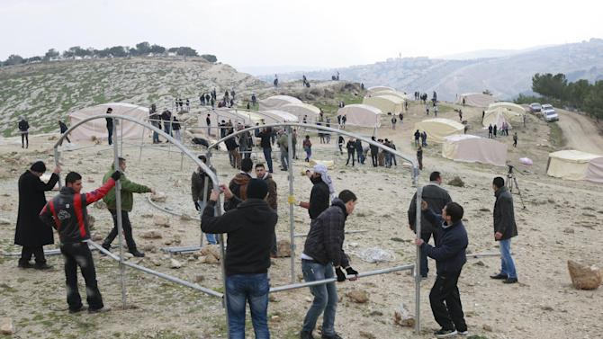 Palestinians, together with Israeli and foreign activists, erect the steel frame of a tent in the new 'outpost ' of Bab al-Shams (Gate of the Sun) in an area known as E1 near Jerusalem, Friday, Jan 11, 2013. In the background the Israeli settlement of Ma'aleh Adumim is seen. Palestinian activists pitched tents in the West Bank on Friday to protest Israeli plans to build a large Jewish settlement on a key route through the territory. The E-1 settlement would block east Jerusalem from its West Bank hinterland — both territories captured by Israel during the 1967 Mideast war. (AP Photo/Majdi Mohammed)