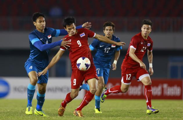 Muhammad Afis of Singapore and Adisak of Thailand fight for the ball uring the soccer semi-final match at the 27th SEA Games in Naypyitaw