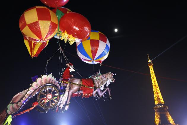 Helium-filled balloons suspend a Santa Claus figure riding a horse-drawn chariot near the Eiffel Tower in Paris