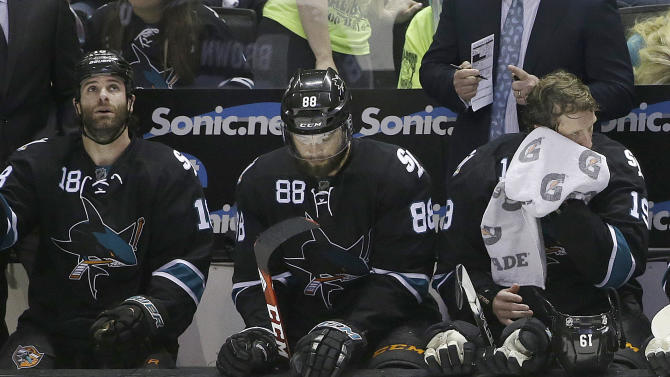 San Jose Sharks right wing Mike Brown, from left, defenseman Brent Burns, and center Joe Thornton sit on the bench during the third period of Game 7 of an NHL hockey first-round playoff series against the Los Angeles Kings in San Jose, Calif., Wednesday, April 30, 2014. The Kings won 5-1. (AP Photo)