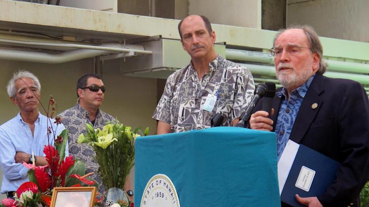 Hawaii Gov. Neil Abercrombie, right, speaks at a gathering in memory of state Health Department Director Loretta Fuddy, as Deputy Director Gary Gill, second from right, listens in Honolulu on Thursday, Dec. 12, 2013. Fuddy died in a plane crash off Molokai on Wednesday. (AP Photo/Audrey McAvoy)