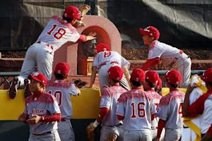 Japan players leap onto the centerfield fence to touch…