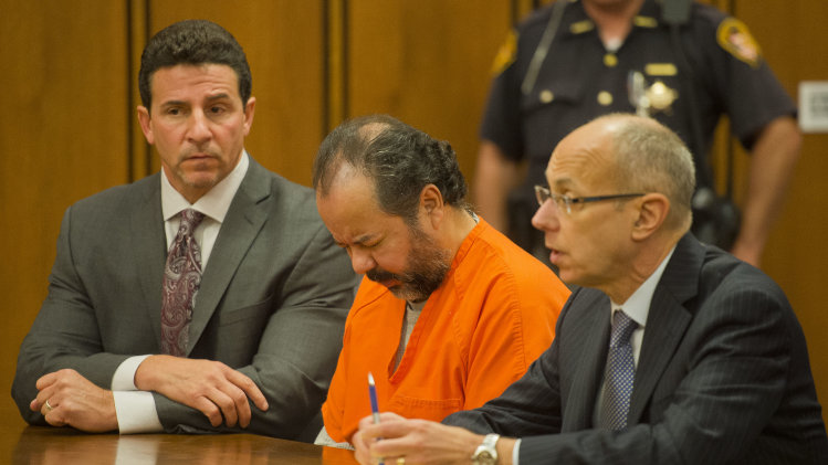 Ariel Castro, center, enters the court before a judge with his defense attorney's, Craig Weintraub, left, and Jaye Schlachet during a pretrial hearing on Wednesday, June 19, 2013, in Cleveland. A tentative Aug. 4 trial date has been set for Castro, accused of kidnapping three women and holding them in his home for about a decade.  (AP Photo/Jason Miller)